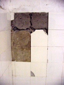 A close-up of the wall where four tiles have been removed