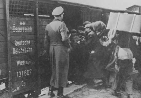 "Jews being loaded into a boxcar to be transported to the Belzec ""extermination camp."""