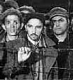 Closeup of man in the center of the photo at the Buchenwald fence