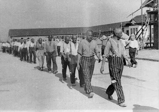 Prisoners at Dachau, on their way to work, are marching to music