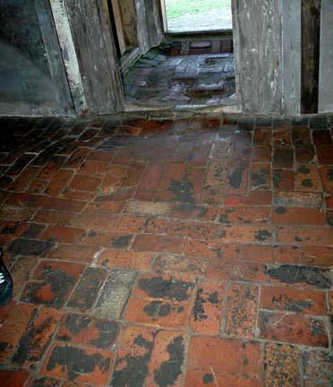 Uneven brick floor inside one of the brick barrack buildings