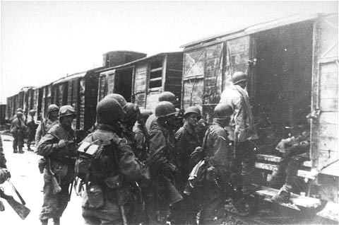 "U.S. soldiers view the bodies of SS men who were taken to the ""death train"" and shot"