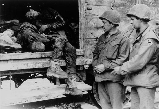 American soldiers pose beside the bodies of SS soldiers killed during the liberation of Dachau