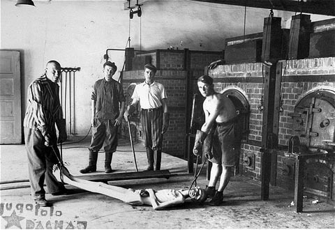 Posed photo of Dachau crematorium workers demonstrating how they put bodies into the oven