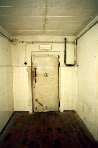 Door into Mauthausen gas chamber shows water pipe going from morgue into the gas chamber