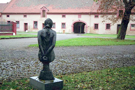 Statue of woman with hands tied behind her back