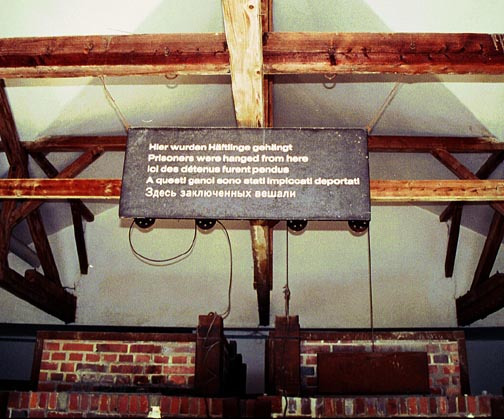 Sign above the ovens at Dachau says that prisoners were hung from hooks