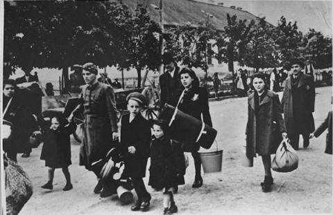 Jews carrying their luggage from train station to Theresienstadt ghetto