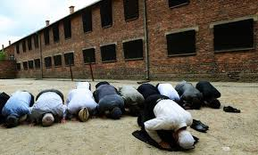 Muslims bow their head to the ground in front of the Black Wall at Auschwitz