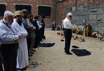 Muslim leaders pray at the Black Wall in the Auschwitz main camp