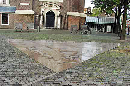 A pink triangle at ground level in front of the same church in Amsterdam