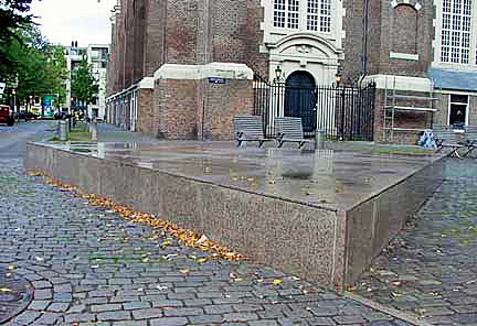 A pink triangle monument in front of a church in Amsterdam