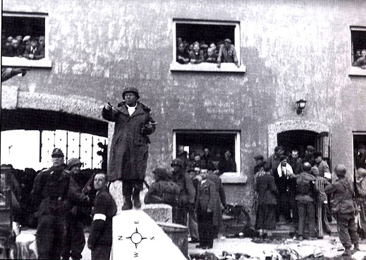 General Linden standing at the gate into Dachau after the camp was surrendered