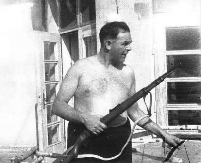 Amon Goeth standing on the patio of his house, holding a rifle