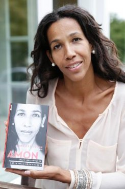 "Nigerian-German author Jennifer Teege poses for a photo with her book ""Amon, My grandfather would have shot me"" about concentration camp commander Amon Goeth on September 26, 2013, Hamburg"