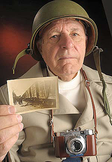 "Donald Burdick holds a photo which he took with a ""liberated"" German camera"