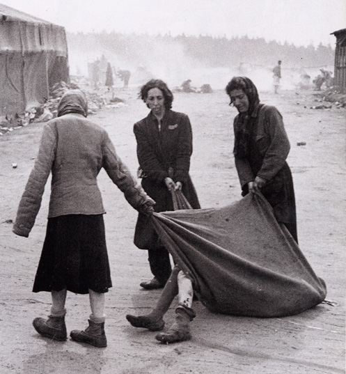 Jewish prisoners dragging a dead body at Bergen-Belsen