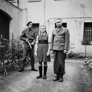 Irme Grese and Kramer are guarded by a British soldier at the Bergen-Belsen concentration camp