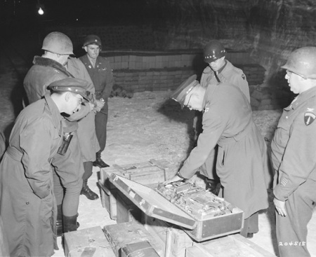 General Eisenhower looks at gold found in suitcases inside Merkers mine