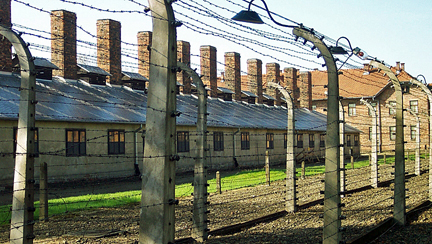 Fence around the main Auschwitz camp with camp kitchen in background