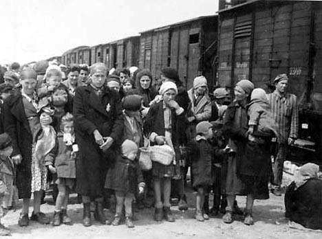 A Kapo standing beside a train that has just arrived at Auschwitz-Birkenau