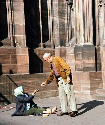 Woman begging for money outside a church in Strasbourg, France