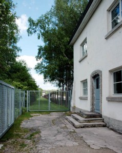 Gatehouse at Dachau with fence between the gate and the gas chamber location