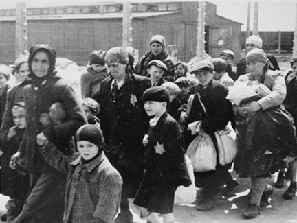 Jews carrying  their bundles as they walk to the gas chamber