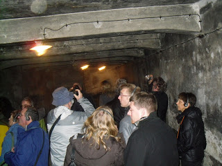 A tour group inside the gas chamber in the main Auschwitz camp