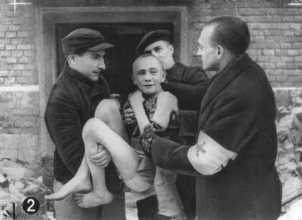 Young boy being carried out of an Auschwitz barrack by Russian soldiers