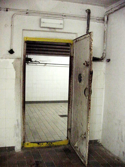 One of the two doors into the gas chamber with water pipe on  the wall