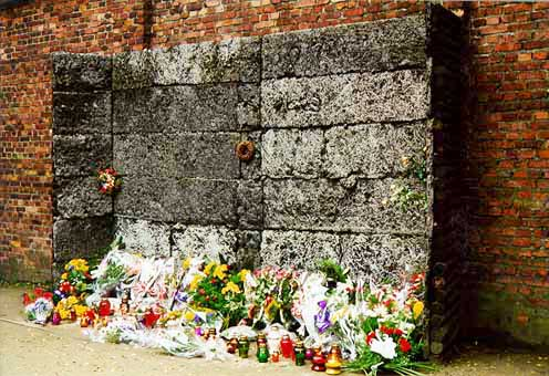 """Tourists may place flowers at the """"black wall"""" at the Auschwitz main camp"""