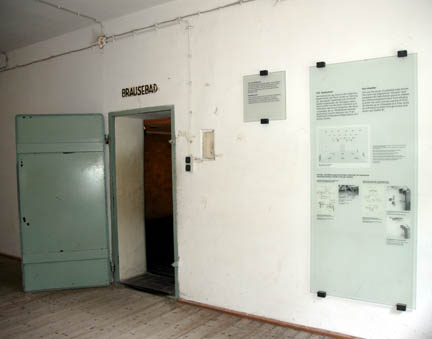 Signs on wall next to the door into the Dachau gas chamber