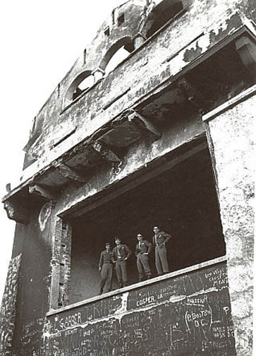American soldiers stand at the picture window of the Berghof after the building was destroyed
