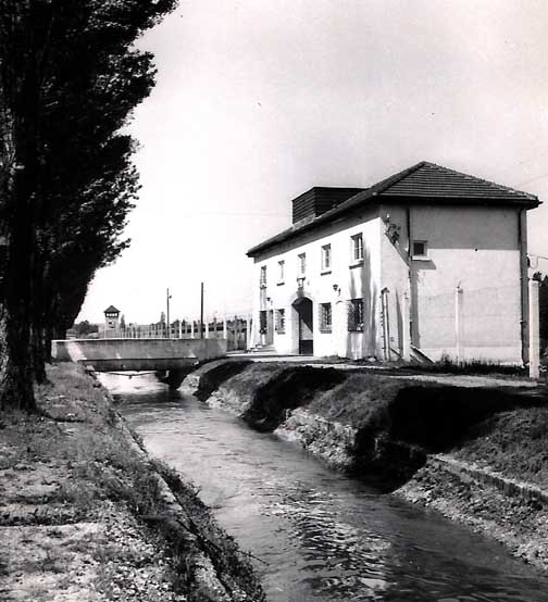 A bridge over Würm river canal leads to the Dachau gatehouse on the right