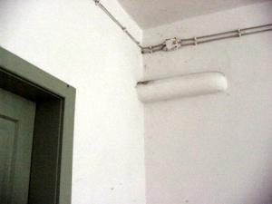 The wall of the undressing  room at Dachau shows a pipe going into the gas chamber