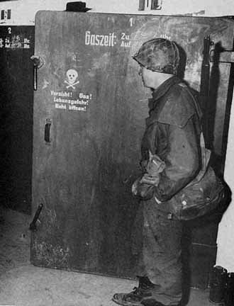 American soldier looks at the door into a disinfecion chamber at Dachau after the camp was liberated