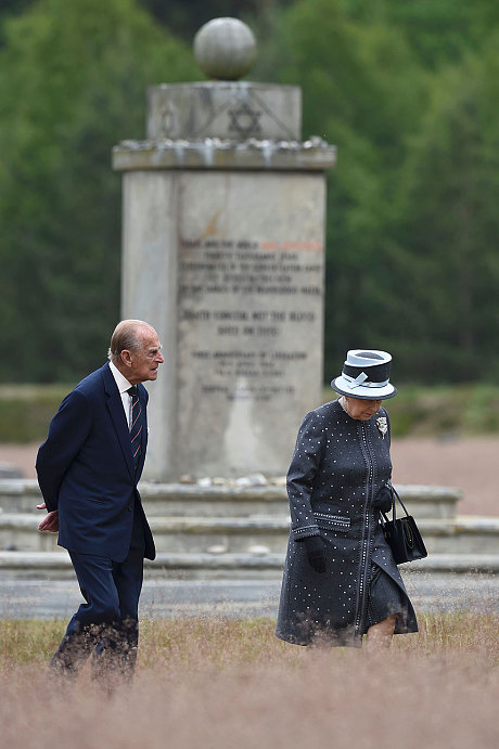 Queen Elizabeth and Prince Phillip pass by the memorial stone to the Jews