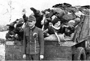 Franz Hoessler standing in front of a wagon load of dead bodies at Bergen-Belsen