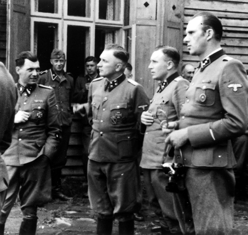 Dr. Josef Mengele is the man on the far left, surrounded by his entourage