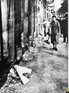 German man sweeping up broken glass after Kristallnacht