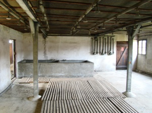 The shower room at Majdanek with a concrete bathtub in the background
