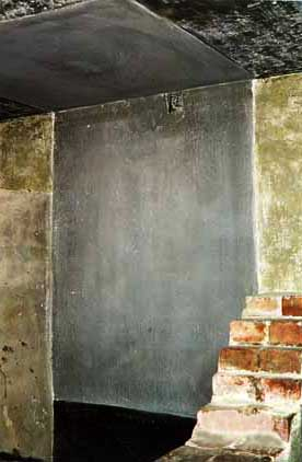 Standing cell with wall cut away so visitors can see inside