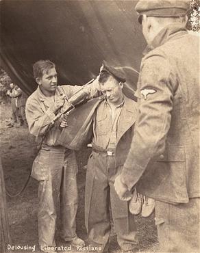 American soldier sprays a Dachau inmate with DDT