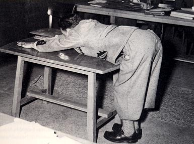 Rudolf Wolf, a former prisoner at Dachau, demonstrates the whipping block at the Dachau trial of Franz Trenkle