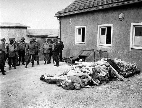Black soldiers look at the bodies of priosoners who died at Buchenwald