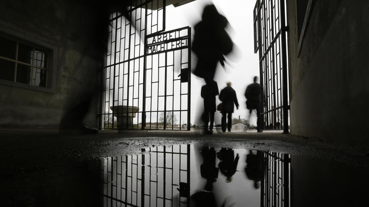 People are reflected in a puddle as they walk through the gate of the Sachsenhausen Nazi death camp with the phrase 'Arbeit macht frei' (work sets you free) at the International Holocaust Remembrance Day, in Oranienburg, about 18 miles north of Berlin, on Jan. 27, 2016. (Markus Schreiber / AP)