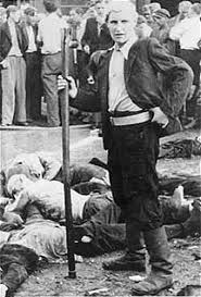 Lithuanian man standing near the bodies of Jews that he has killed