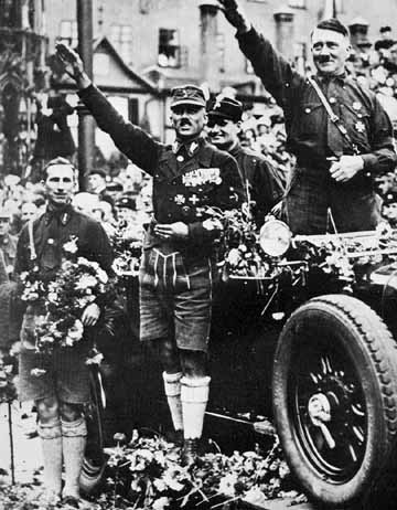 Adolf Hitler gives a Nazi salute in 1927