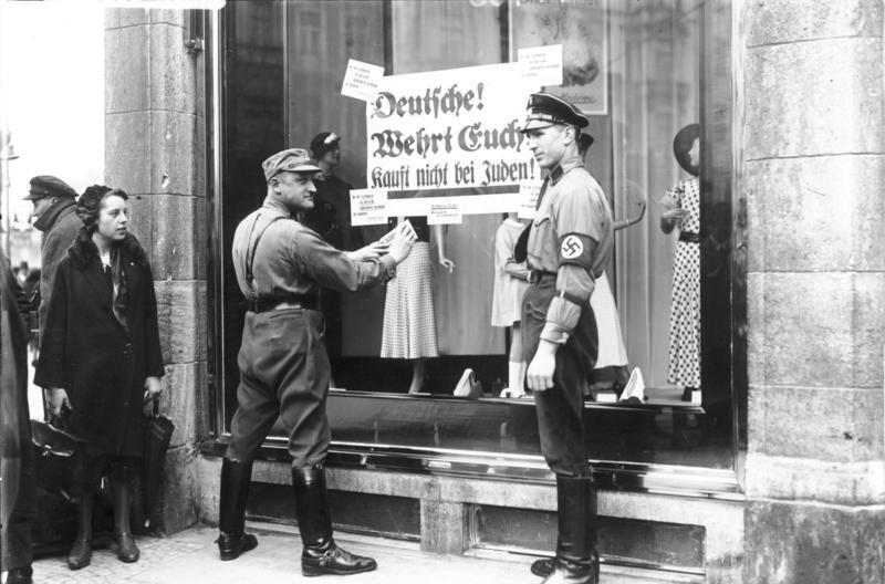 """An den Fenstern jüdischer Geschäfte werden von Nationalsozialisten Plakate mit der Aufforderung """"Deutsche, wehrt euch, kauft nicht bei Juden"""" ."""